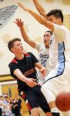 <p>Liberty Charter's Michael Wachsmuth, left, passes away from a Lapwai double team in the second half of the state boys basketball opening round game Thursday afternoon at Vallivue High School. Lapwai won 60-29. Thursday, March 5, 2015 (Greg Kreller/IPT)</p>