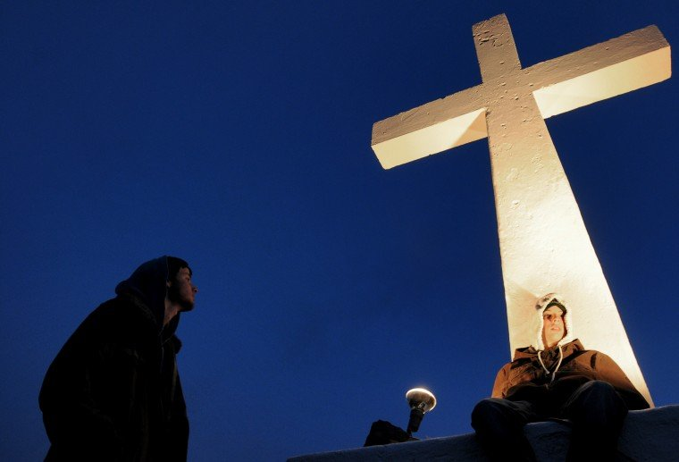 Andrew Van Horn, 16, of Marsing, sits below the cross as his brother, ...