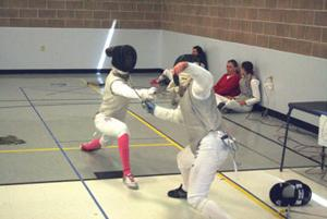 <p>Marissa Nelson, left, battles her opponent in a fencing match on Saturday at the Pocatello Community Charter School on South Arthur Avenue.</p>