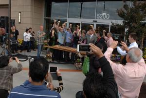 Officials took part in the grand opening of the new Whole Foods Market in Dublin. As part of the ceremonies, those attending were invited to share the loaf of bread (Photos - Doug Jorgensen).
