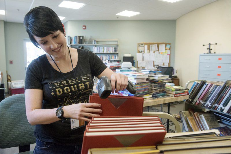 Darcy B. Wood, circulation manager at the Carthage Public Library, processes books on Friday at the library. GLOBE | ROGER NOMER