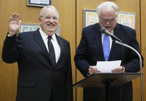 <p>New Mayor Tim Barker is sworn in by City Attorney Paul Webb during Monday's Wharton City Council meeting.</p>