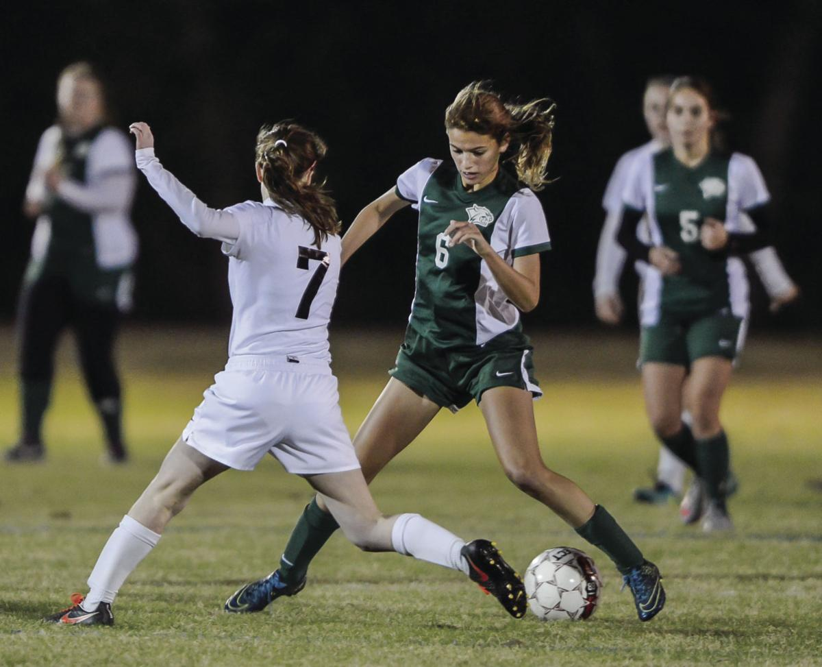 Walker's Haley Marshall (6) attempts to make her way around St. Michael defender Brittany Segalla (7) while dribbling toward the Warrior's goal on Tuesday.