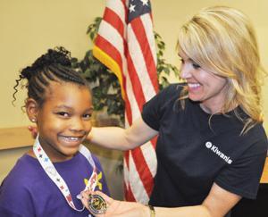 <p>Debbie Coe of the Kiwanis Club of Denham Springs presents a gold medal to Mathletes participant Kaylan Williams of Denham Springs Elementary School.</p>