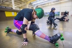 Reporter Skates After Her Derby Girl Dreams : After a few laps around the rink, News-Sentinel reporter Sara Jane Pohlman stretches with members of the Port City Roller Girls roller derby team at the San Joaquin County Fairgrounds on Thursday, Feb. 7, 2013.  - Photo by Dan Evans/News-Sentinel