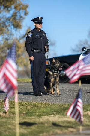 Fallen Galt Police Officer Kevin Tonn Laid To Rest : Officer Brian Niño stands with Yaro, Galt Police Officer Kevin Tonn's dog, during the graveside service for Tonn on Monday, Jan. 21, 2013.  - Photo by Dan Evans/News-Sentinel