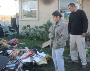 Lodi Couple Homeless After Fire Destroys Home: Joanna and Juan Ruiz look over what's left of their home that was destroyed by fire Saturday, Nov. 10, 2012. The couple was at a family reunion in Lathrop when the house off Lower Sacramento Road, south of Century Boulevard, erupted in flames.  - Photo by Ross Farrow/News-Sentinel