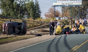 High-speed Chase Ends In Crash: Emergency workers attend to the victims of a high-speed chase after it ended with a rollover accident on the Highway 99 frontage road at Acampo and Peltier roads on Tuesday, Nov. 13, 2012.  - Dan Evans/News-Sentinel