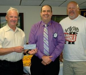 Lodi Sunrise Rotary Club President Richard Ross presents Michael Phillips and Anthony Rodriguez with a chek for the Lodi High School Track renovation project