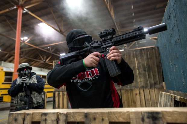 <p>Ryan Daugherty, 16, of Lodi shoots at an opponent while taking cover behind a pallet wall during an Airsoft match at CQB City in Stockton on Sunday, Feb. 2, 2014.</p>