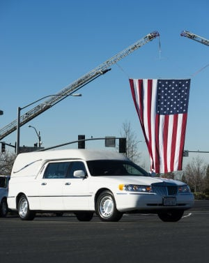 Fallen Galt Police Officer Kevin Tonn Laid To Rest : An American flag waves in the wind as the funeral procession arrives at Adventure Community Church in Roseville where the funeral for Galt Police Officer Kevin Tonn was held on Monday, Jan. 21, 2013.  - Photo by Dan Evans/News-Sentinel