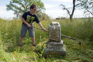 Galt firefighter Eric Schneider works to clean up historic cemetery