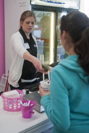 Father-daughter Duo Open Lodi Froyo Shop: Charity Pollock hands a customer her change at Yogurt In Love, a new frozen yogurt store in Lodi, on Friday, Feb. 15, 2013.  - Photo by Ian Jonson/News-Sentinel