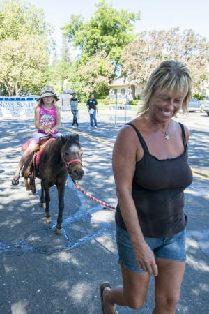Little Buckaroos Saddle Up To Read At The Reading Roundup : Elsie Greenich leads Savannah Stapleton, 8, on a pony ride during the second annual Little Buckaroos Reading Roundup Literacy Fair, hosted by the Lodi News-Sentinel and the Lodi Public Library, on Locust Street in Downtown Lodi on Saturday, Aug. 24, 2013. - Ian Jonsson/News-Sentinel