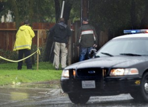 Suspect In Galt Animal Control Shooting Arrested: Law enforcement officers peer over a fence toward a home where a fatal shooting of a Sacramento animal control officer Wednesday, Nov. 28, 2012, in Galt.  - Photo by AP Photo/The Sacramento Bee, Randy Pench