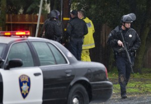 Suspect In Galt Animal Control Shooting Arrested: A police officer carries his assault rifle, right, while other law enforcement officers peer over a fence, background, toward the home where a Sacramento animal control officer was fatally shot Wednesday, Nov. 28, 2012, in Galt.  - Photo by AP Photo/The Sacramento Bee, Randy Pench