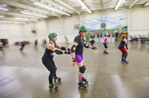 "Reporter Skates After Her Derby Girl Dreams : With instruction from ""Malice,"" left, of the Port City Roller Girls roller derby team, slowly pushes News-Sentinel reporter Sara Jane Pohlman to teach her proper skating technique at the San Joaquin County Fairgrounds on Thursday, Feb. 7, 2013.  - Photo by Dan Evans/News-Sentinel"