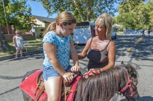Little Buckaroos Saddle Up To Read At The Reading Roundup : Elsie Greenich helps Amelia Dietz, 8, onto a pony for a ride during the second annual Little Buckaroos Reading Roundup Literacy Fair, hosted by the Lodi News-Sentinel and the Lodi Public Library, on Locust Street in Downtown Lodi on Saturday, Aug. 24, 2013. - Ian Jonsson/News-Sentinel