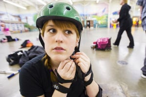 Reporter Skates After Her Derby Girl Dreams : News-Sentinel reporter Sara Jane Pohlman puts on an ill-fitting helmet before taking to the rink with the Port City Roller Girls roller derby team at the San Joaquin County Fairgrounds on Thursday, Feb. 7, 2013.  - Photo by Dan Evans/News-Sentinel