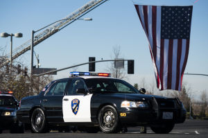 Fallen Galt Police Officer Kevin Tonn Laid To Rest : A Galt police car passes by a large flag at the entrance of Adventure Community Church where the funeral for Officer Kevin Tonn was held on Monday, Jan. 21, 2013.  - Photo by Dan Evans/News-Sentinel