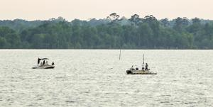 <p>Two boats on Saturday night mark and watch an area on Sam Rayburn Reservoir where a Huntington man drowned hours earlier.</p>