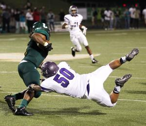 <p>Lufkin Panthers linebacker Ariel Olivera dives to try to make a tackle on Longview running back Tylan Miller in the second half of the teams' game Friday night at Lobo Stadium in Longview.</p>