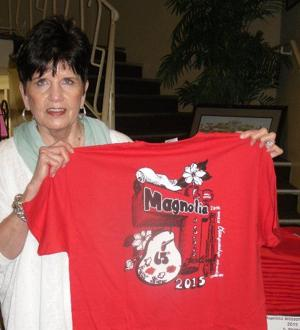 <p>Jennifer Hubbard holds an official Magnolia Blossom Festival T-shirt -- the back of the T-shirt is shown.</p>