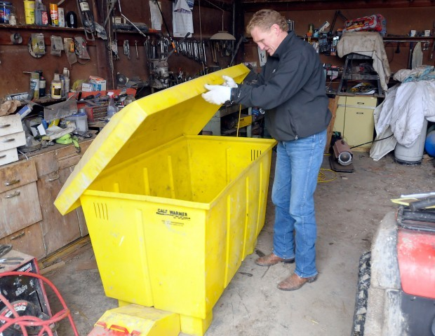 Jack Stivers opens a calf warming box