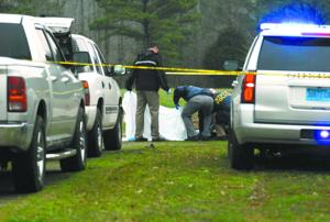 <p>Alabama Bureau of Investigation officers examine the body of Shane Watkins while another holds up a sheet to block the view last Thursday morning. Watkins was fatally shot by a sheriff's investigator who responded to a domestic call. Sheriff Gene Mitchell said Watkins charged the officer with a box cutter before he was shot.</p>