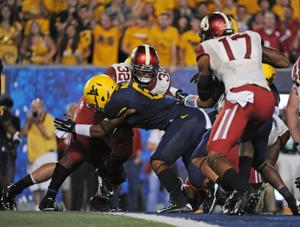 <p>Oklahoma's Samaje Perine, back, crosses the goal line for a touchdown as teammate Jordan Smallwood, right, blocks in the second quarter of Saturday's game against West Virginia in Morgantown, W.Va. Perine ran for 242 yards as the No. 4 Sooners beat the Mountaineers 45-33.</p>