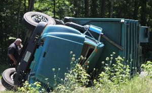 Garbage truck rolls over