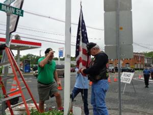 <p>From left, Paul Lingsch and Tom Bender raise the flag.</p>