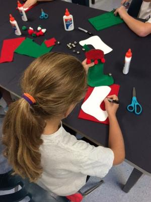 <p>An Assumption School 4th grader is at work on Christmas stocking decorations for the Macculloch Hall Drawing Room tree.</p>