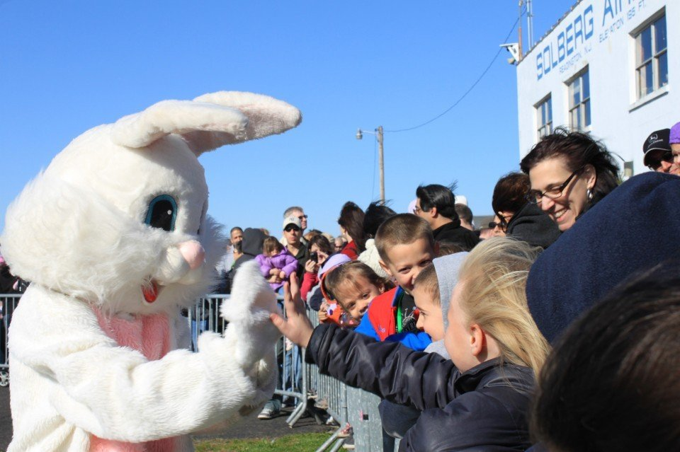 The Easter Bunny high fives the crowd