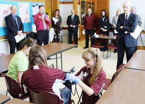 <p>Wisconsin State Superintendent Tony Evers (at right) watches as students in the School District of Ladysmith Health Care Academy show some of the skills they have learned in the academy's EMT training classes.</p>