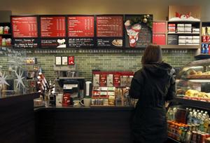 <p>A customer places an order at a Starbucks in Chicago. Areas by cash registers are often crowded with little extras in part because the closer a customer is to an item, the more likely they are to make an impulse buy.</p>
