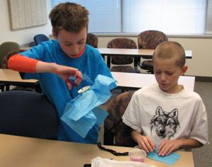 <p>Aaron Hawley and Reynger Daeidsaeo assemble parachutes out of simple materials at USU's Science and Engineering Kids Day.</p>