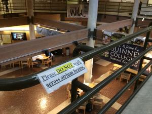 <p>A sign on a railing overlooking the atrium in USU's Natural Resources Building warns students not to walk across the atrium beams.</p>