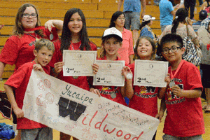 <p>Wildwood Elementary students hold up their certificates with pride.</p>