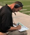 Merrillville head coach Zac Wells looks over some plays on the sidelines Saturday.