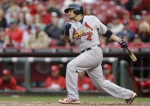 Cardinals hold on to edge Reds