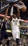 Pacers center Ian Mahinmi dunks as Pelicans forward Anthony Davis defends during the first half Saturday.
