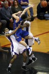 Merrillville's Isaiah Wilson draws the player control foul against Carmel's Michael Volovic on Saturday.