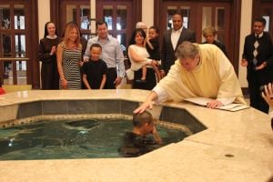 School gathers as siblings are baptized