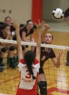 Chesterton's Jessica Urycki spikes past the block of Crown Point's Morgan Chacon