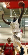 Bishop Noll's Marquis Tarver drives past Lake Station's Brian Patterson during Saturday's GSSC title game.