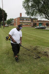 Workers trim grass at Dunbar-Pulaski Middle School in Gary.