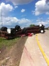 Semitrailer rolls over, loses load