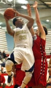 Bishop Noll's Tyreon Gates drives into Lake Station's Mark Novakovich during Saturday's GSSC tourney final.