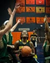 Marian Catholic's Taylor Bailey takes on a trio of Fremd defenders as she drives to the basket Saturday.